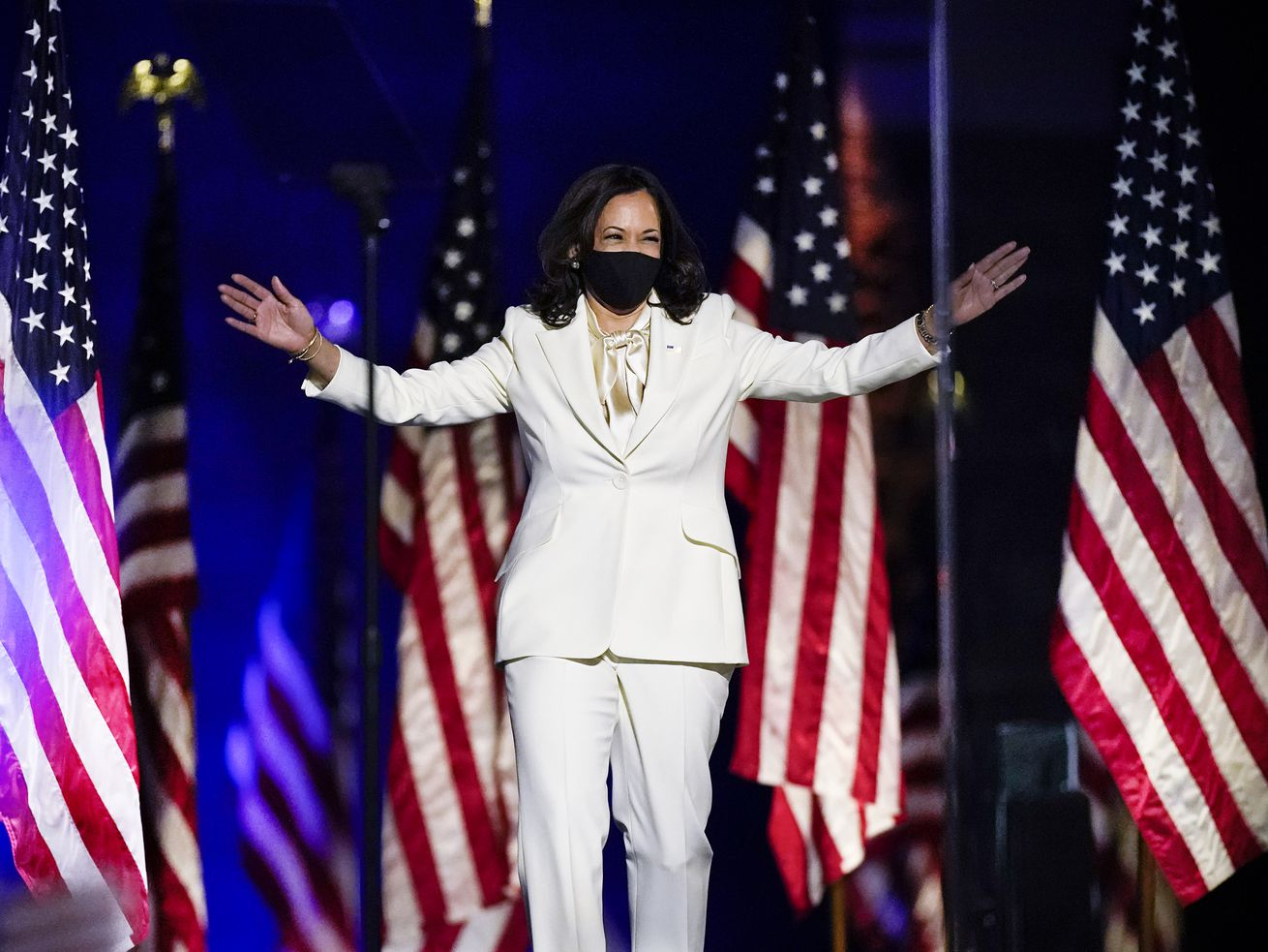 Harris spreads her arms as if hugging the crowd before her in a well tailored white suit, white silk pussy bow blouse, and black face mask. Behind her is a row of US flags, and she is illuminated by blue spotlights.
