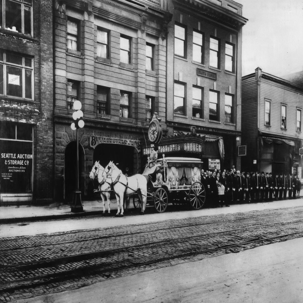 In an old, black-and-white photo, a carriage drawn by two horses is followed by rows of people dressed in black in front of brick three-story buildings.