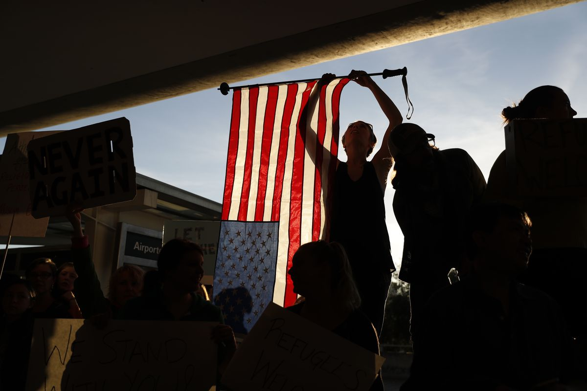 A demonstrator holds an American flag during a rally against Muslim immigration ban at San Francisco International Airport on January 28, 2017 in San Francisco, California.
