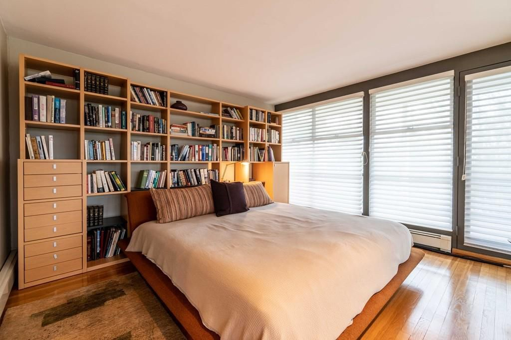 A bedroom with a bed in front of large shelves.