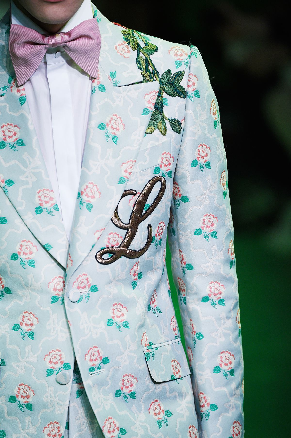 A model walks the runway in a pale blue floral suit with an L monogrammed on the breast.