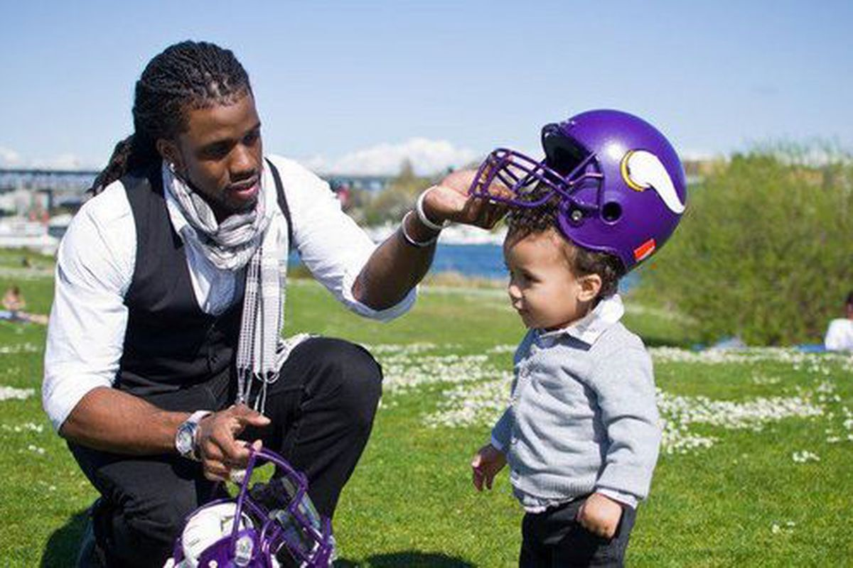 This is the only non-copyrighted picture I could find that has him with Vikings gear, and it's one hell of a picture. That's his son, Dash, learning all that is good and holy.