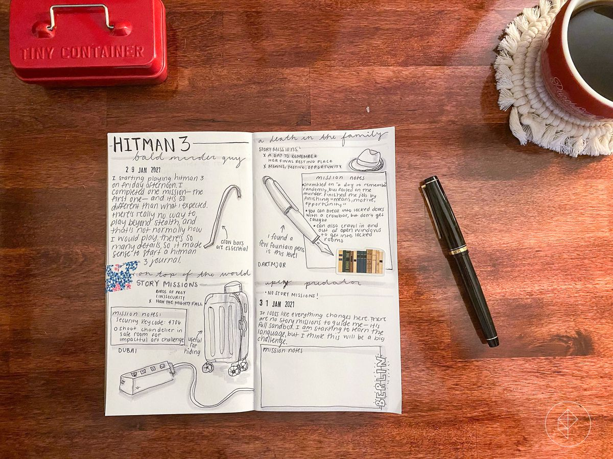 flat lay of a hitman 3 journal with a fountain pen