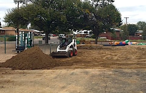 A worker prepares the site for a new preschool playground at Fairview Elementary School.