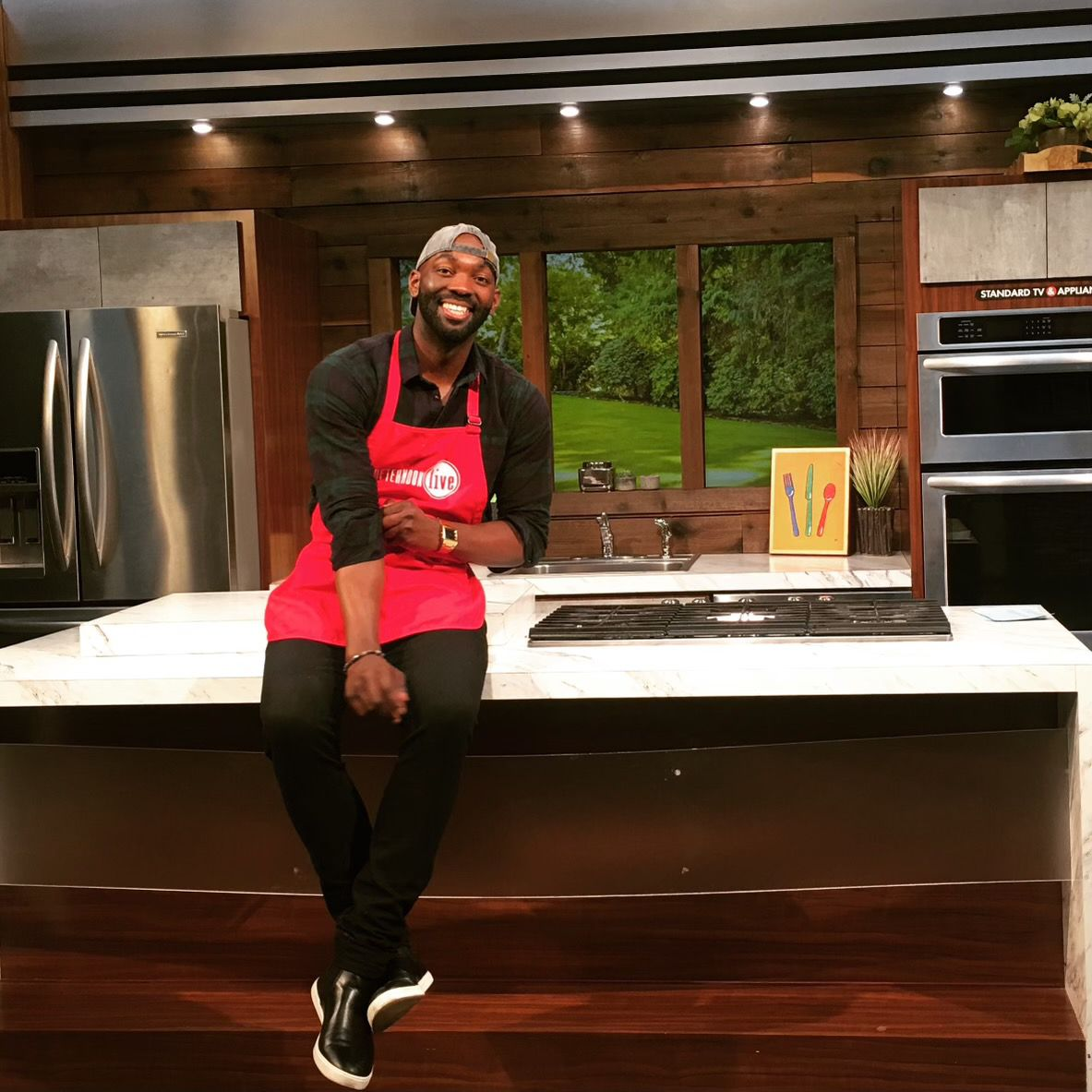 Plant Based Papi owner Jewan Manuel, a man in a backwards baseball cap and an apron, sitting on the counter in a kitchen