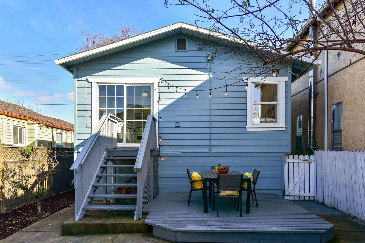 The back side of the home with a wooden deck with table and chairs.