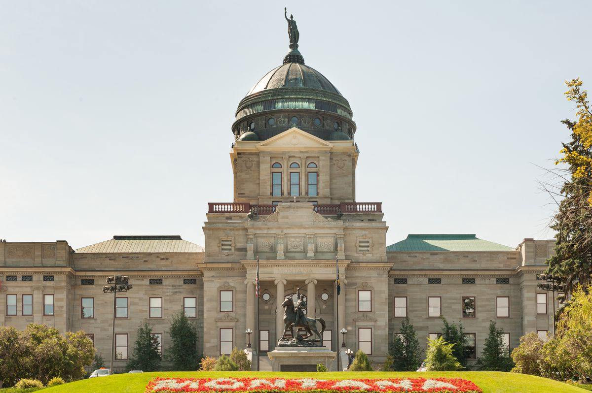 The exterior of the Montana State Capitol. The facade is brown and there is a dark green domed tower with a statue on top. There is another statue in front of the building. The statue is of a person on a horse.