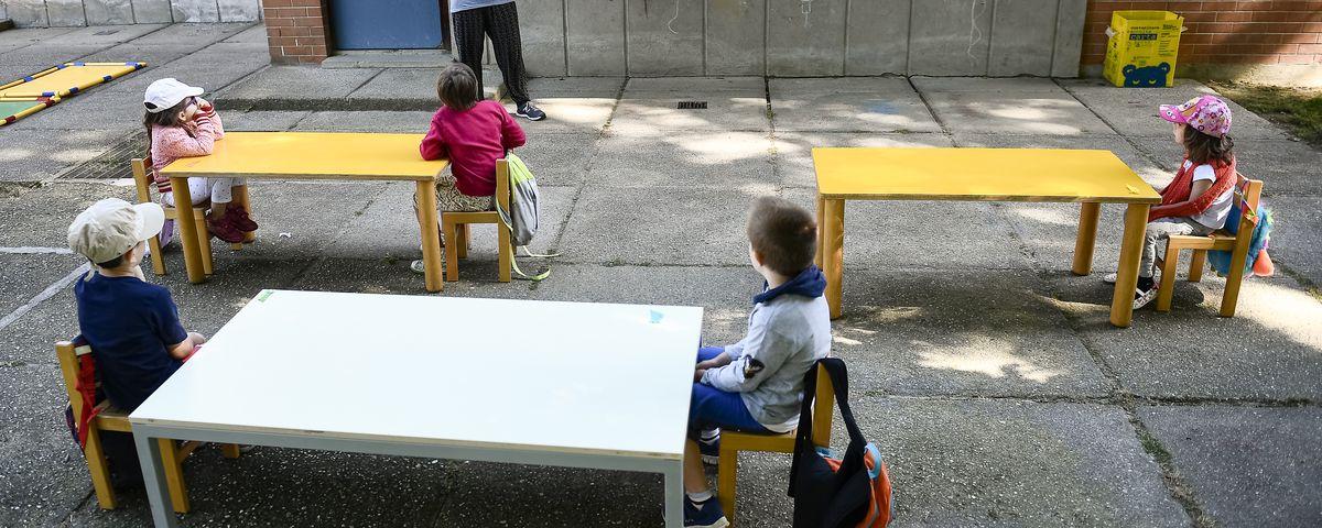 A teacher reads a book to kindergarten children in a school...