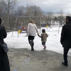 Kerry Coarse, coordinator for support services for the Northwest Primary School, shows Dania Khatib, 5, the school playground as her mother Mahasen Boshnaq, left, and father Ahmed Khatib, right, follow behind in Rutland, Vt. The Syrian refugee family arrived in Rutland this month. Khatib said he looks forward to being self-sufficient, working, having a home for his family and school and clothing for his children.