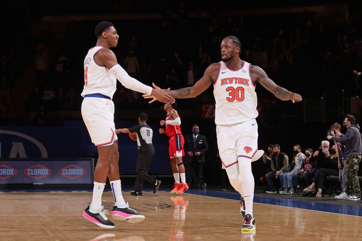 RJ Barrett and Julius Randle of the New York Knicks shake hands against the Washington Wizards on March 25, 2021 at Madison Square Garden in New York City, New York.