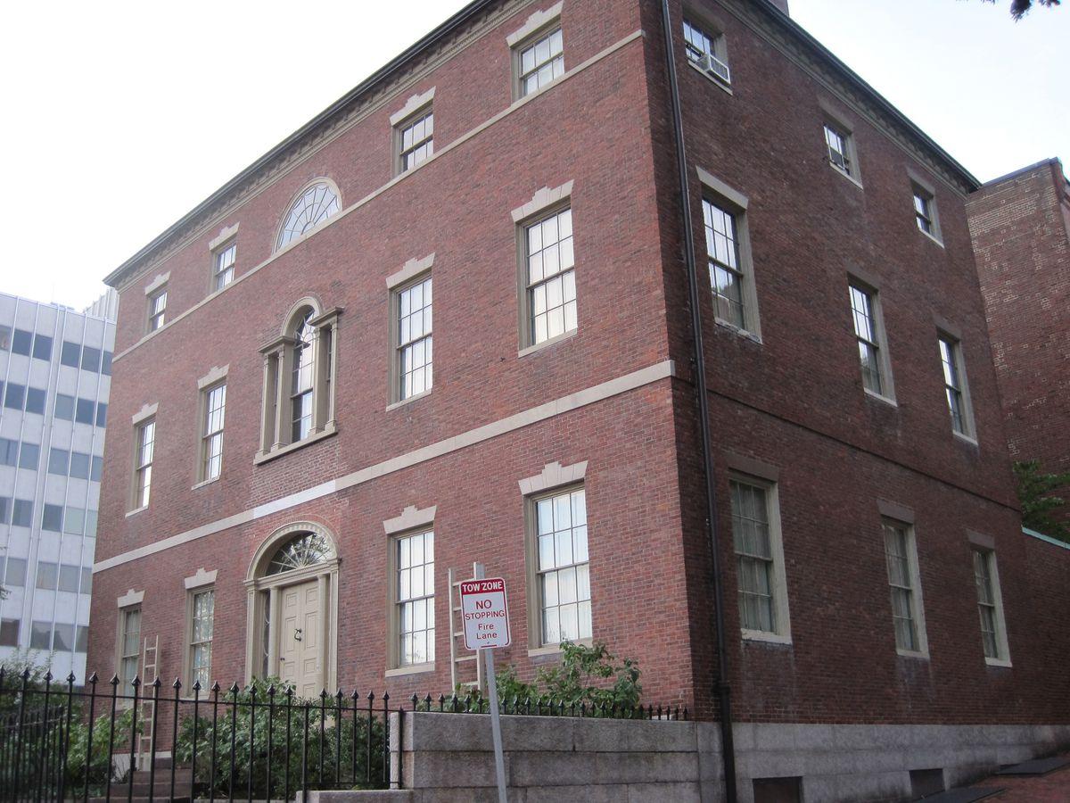 The exterior of a three-story, squarish, brick building.
