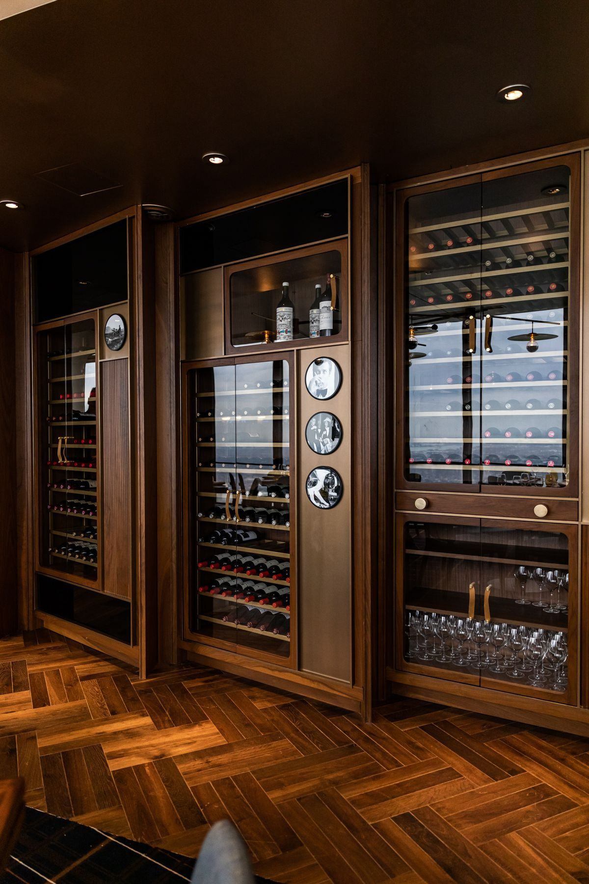 The wood and glass wine case has a mid-century look with circular, vintage black and white photos displayed throughout.
