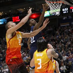 Minnesota Timberwolves' Andrew Wiggins, rear, shoots as Utah Jazz's Rudy Gobert, left, and Ricky Rubio (3) defend during the first half of an NBA basketball game Friday, March 2, 2018, in Salt Lake City. (AP Photo/Kim Raff)