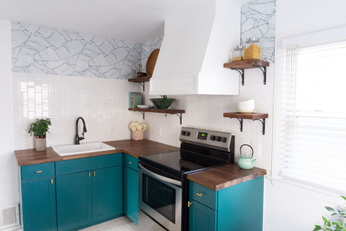 A small kitchen with butcher block counters, turquoise cabinets, and blue tortoise wallpaper.