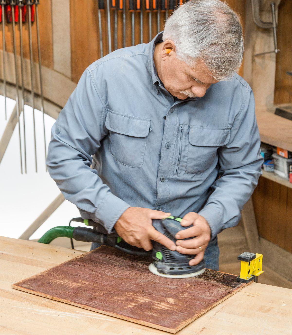 Pessoa usando uma lixadeira orbital aleatória na peça de madeira que formará a parte de trás de uma caixa de sombra.