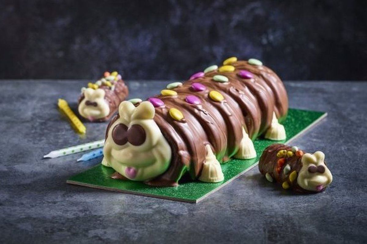 A photo of a chocolate Colin the Caterpillar cake on a dark background