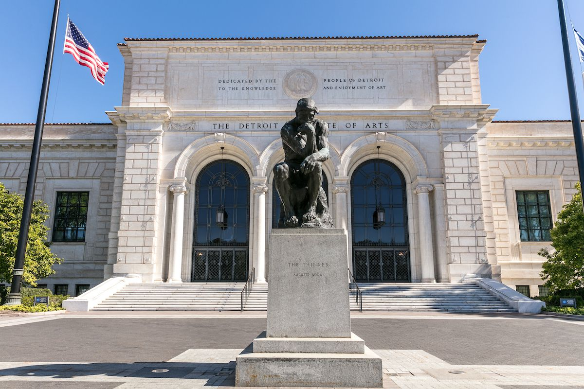 Front entrance of the Detroit Institute of Arts. There's a black statue in front of the double marble arched entrance.