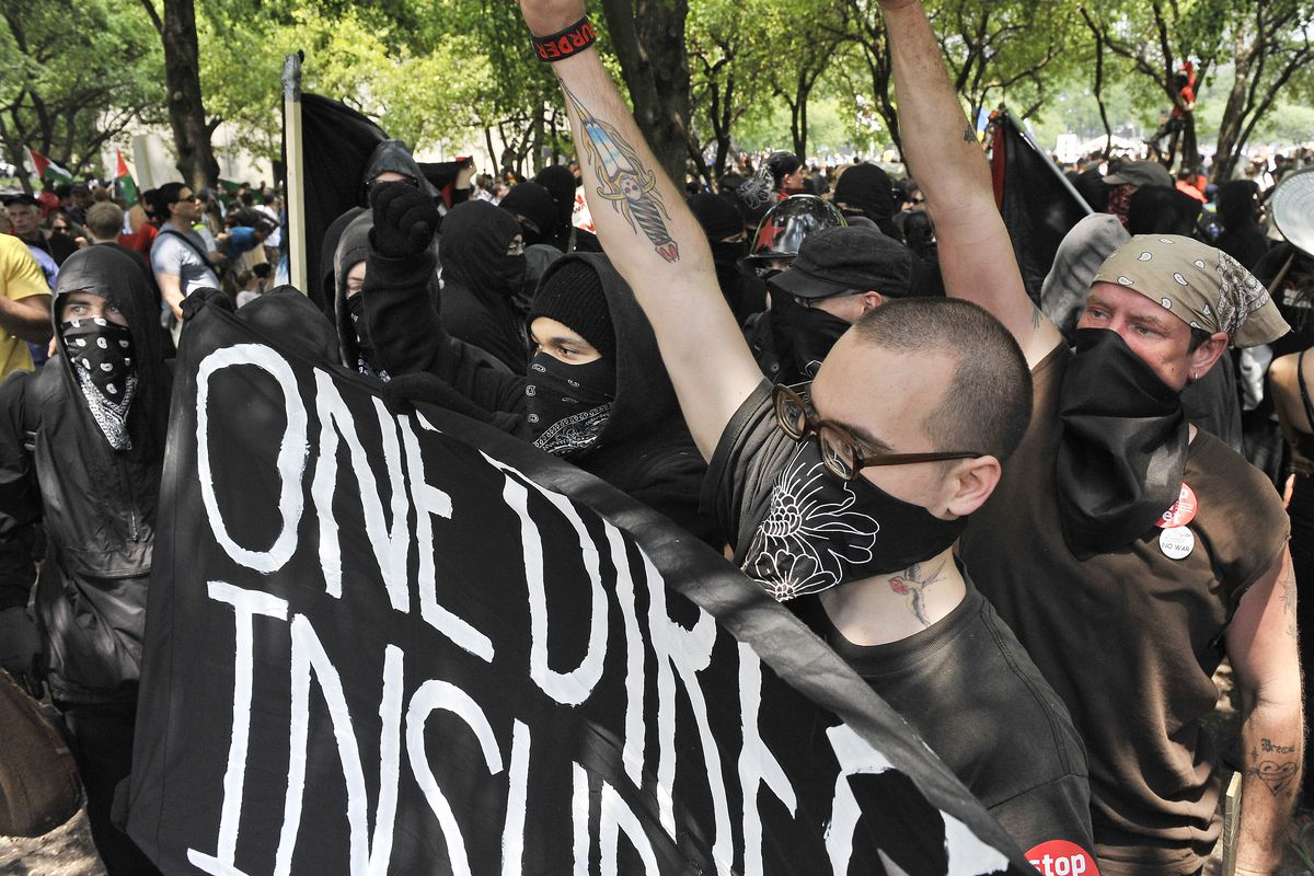 Black Bloc protesters perpare for the start of activities in Grant Park. They tried to prevent themselves from being photographed. |Al Podgorski~Sun-Times