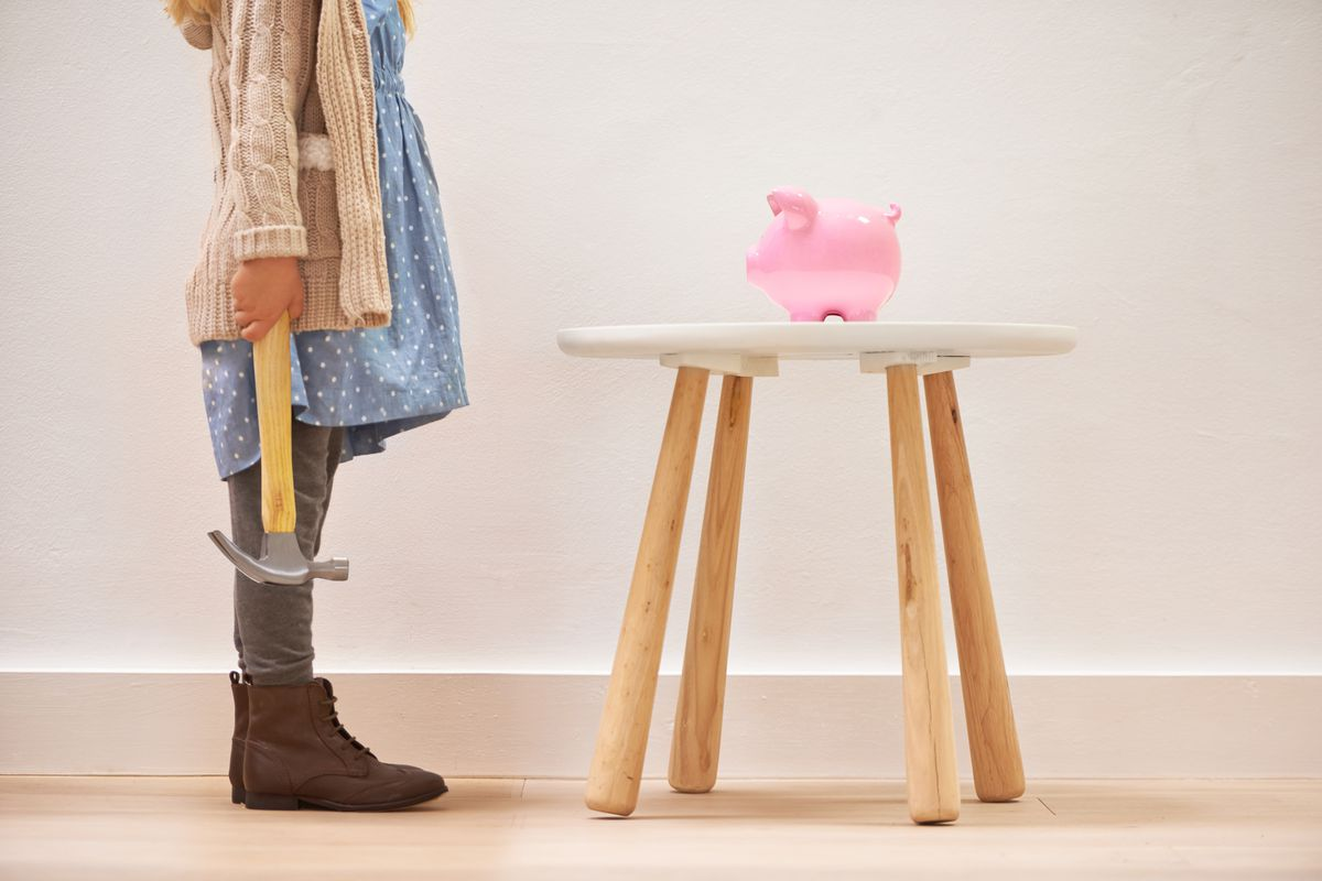 A person in front of a piggy bank holding a hammer.