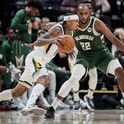 Utah Jazz guard Jordan Clarkson, left runs past Milwaukee Bucks forward Khris Middleton during an NBA preseason game at Vivint Arena in Salt Lake City on Wednesday, Oct. 13, 2021.