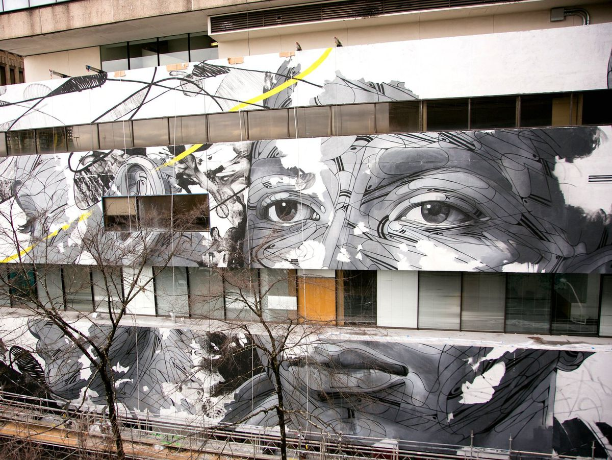 A black and white mural on the side of a building.