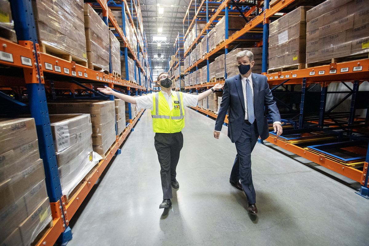 Elder Tyson Jacob Weatherhead, of San Antonio, Texas, describes the size of the Bishops' Central Storehouse to Elder S. Gifford Nielsen, a General Authority Seventy of The Church of Jesus Christ of Latter-day Saints, as workers load trucks with food at the facility in Salt Lake City on Friday, Nov. 13, 2020. The food will be delivered to nine pantries across the country as part of a new partnership between the University of Wyoming's noted Black 14 and the Church of Jesus Christ.