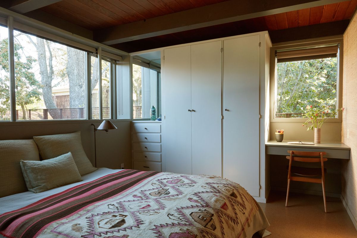 A bedroom. The bed has a patterned quilt and multiple pillows. There is a storage closet and a deck with a chair. There are multiple windows. A lamp sits next to the bed.
