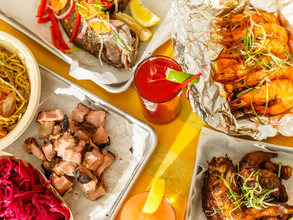 Jerk pork and shrimp sit atop a yellow tabletop at Glady's