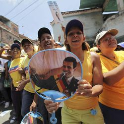 Supporters of opposition presidential candidate Henrique Capriles, one showing an image of him, cheer during a campaign rally in Caracas, Venezuela, Sunday, Sept. 16, 2012. Capriles is running against President Hugo Chavez in the country's Oct. 7 election.