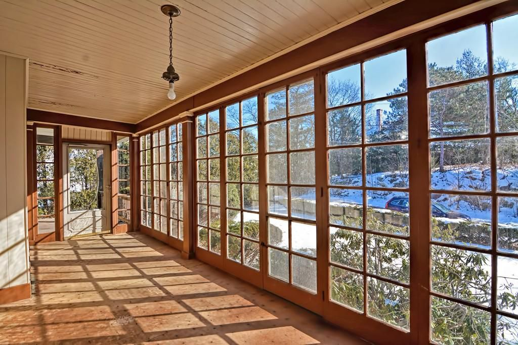 A long, empty sunroom with floor-to-ceiling windows.