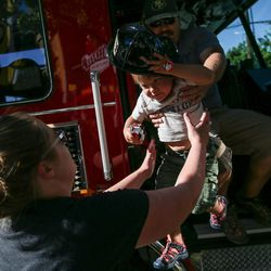 Ryan You passes his son, Ronan, 2, to his wife, Rita You, while the Salt Lake City Fire Department shows off its two new ladder trucks at Smith's Ballpark in Salt Lake City on Tuesday, June 27, 2017.