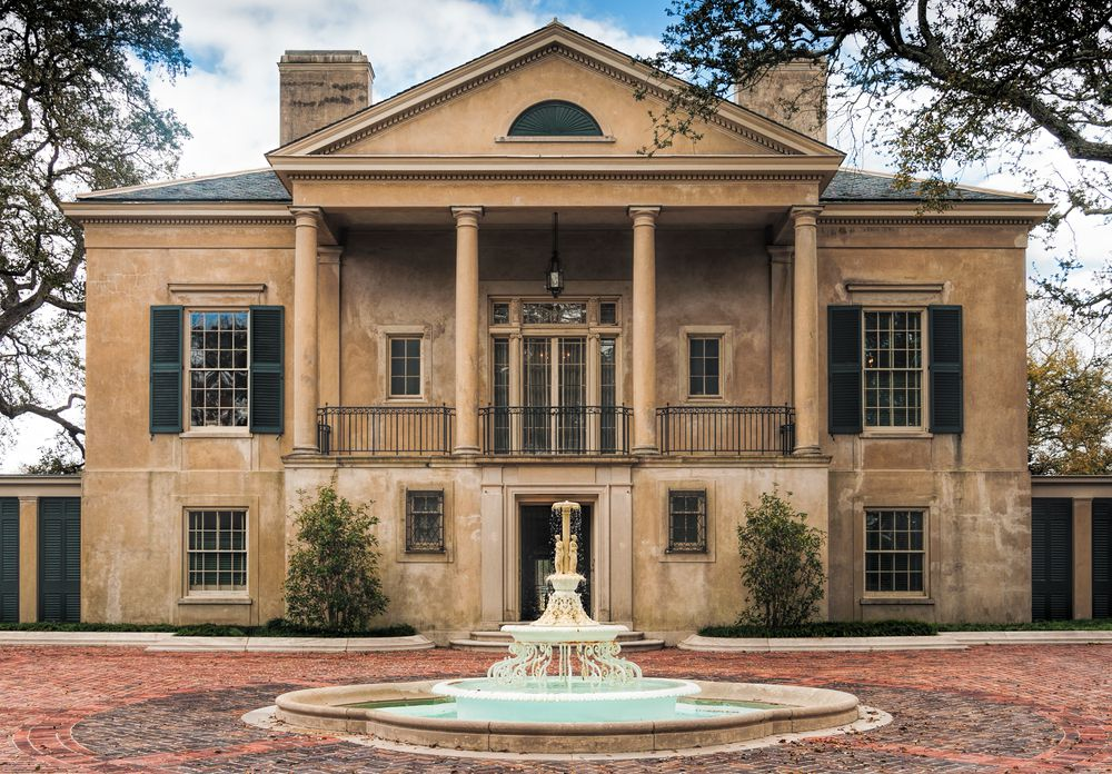 The exterior of the Longue Vue House and Gardens in New Orleans. The facade is tan with columns. There is a fountain in a courtyard in front of the house.