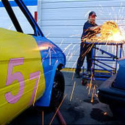 Team Vibrate member Ed Vine cuts a roll bar while working on his rollover car. Team members spend a lot of time and money getting cars ready to roll \\\\— something they do at six to 10 shows each summer.