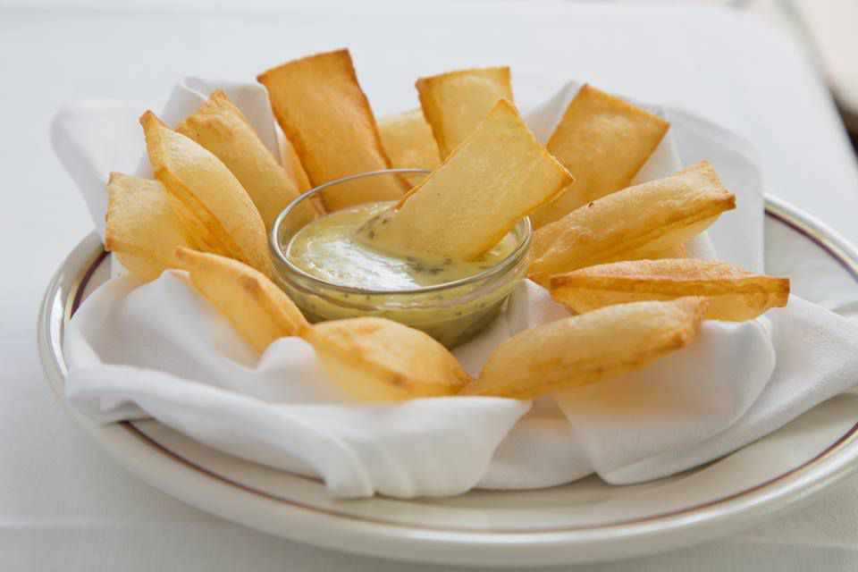 A plate of potatoes fried to look like tiny pillows, puffed up and hollow in the center; served with a green dipping sauce.