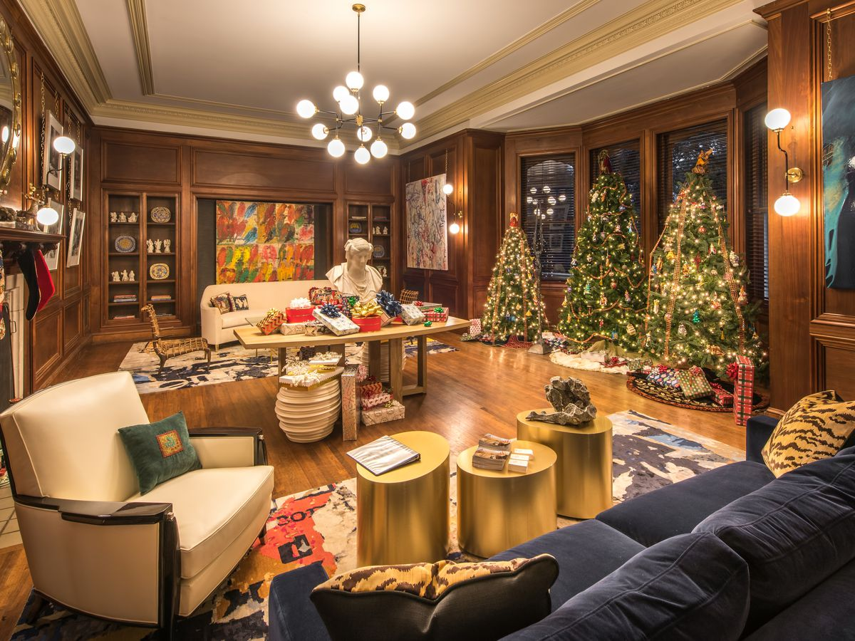 Family room decorated for Christmas with three trees and wrapped gifts.