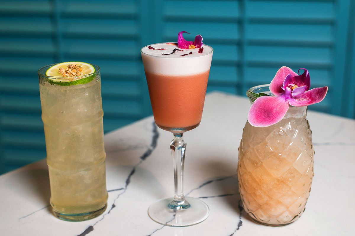 Three tropical drinks with orchids garnishing them.