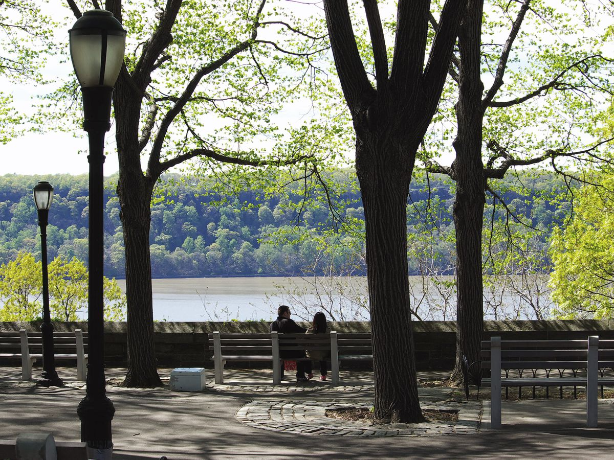 Park benches, trees, and a path in Fort Tryon Park in New York City. In the distance is a body of water.