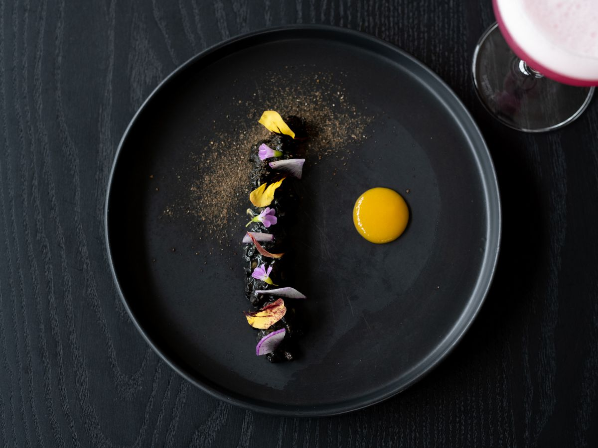 A stark black dish with a black central line of charred bits decorated with pops of yellow and lavender. A pool of golden sauce sits off to the side and a faint dusting of gold powder decorates the top left side of the plate.