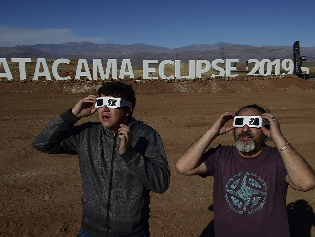 Tourists don special glasses to watch an eclipse at the entrance of an astronomical camp that expects to receive thousands of tourists to observe the July 2 total solar eclipse.