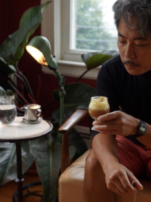 A man sits in a pale orange leather chair, holding and staring at a glass of Vietnamese coffee. A small table, lamp, and plant are visible in the background.