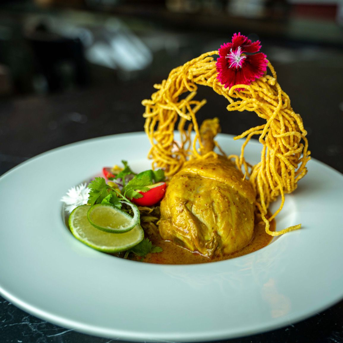 Khao soi gai (noodles with chicken, lime, and quail egg in curry)