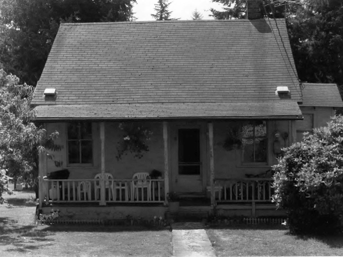A black-and-white photograph of an old house with a tall roof sloping down over a wide front porch.