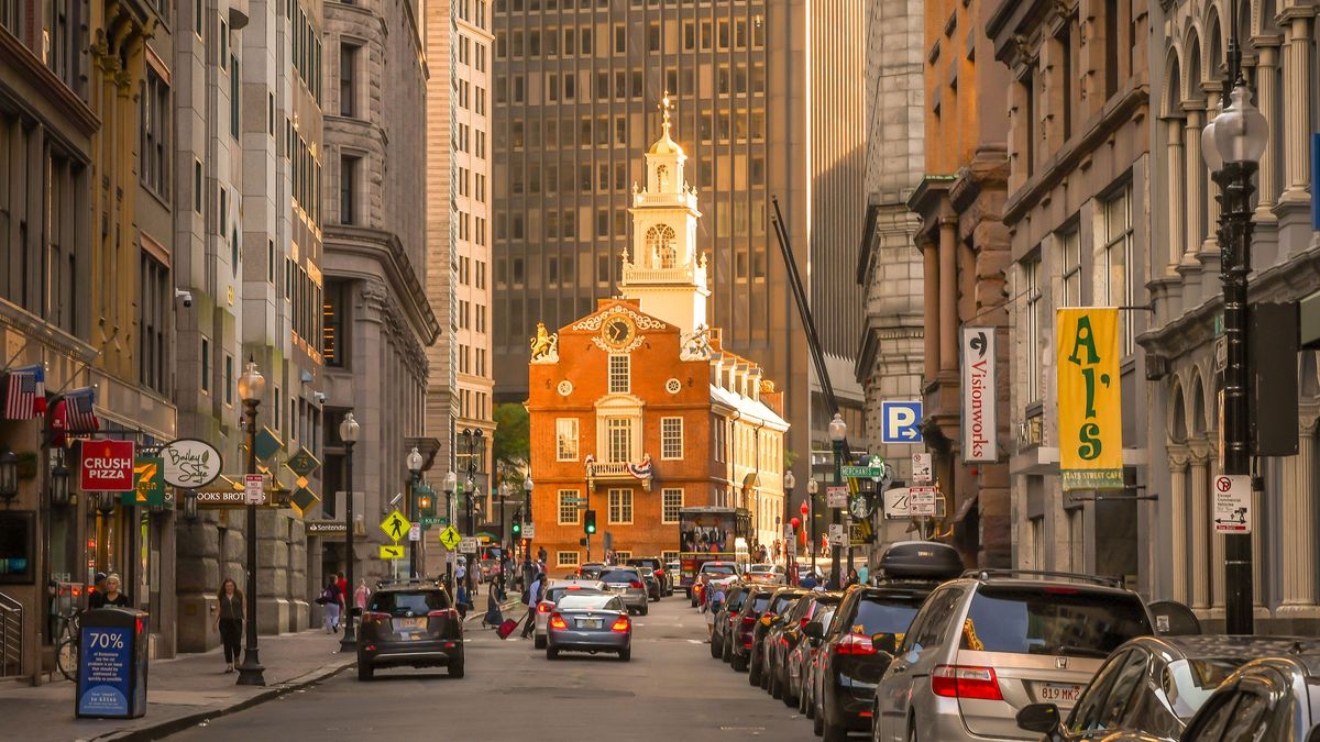A street in Boston. There are cars parked on the street and cars traveling in the middle of the street. Both sides of the street are lined with retail shops. At the end of the street is a historic red building with an ornate white roof.