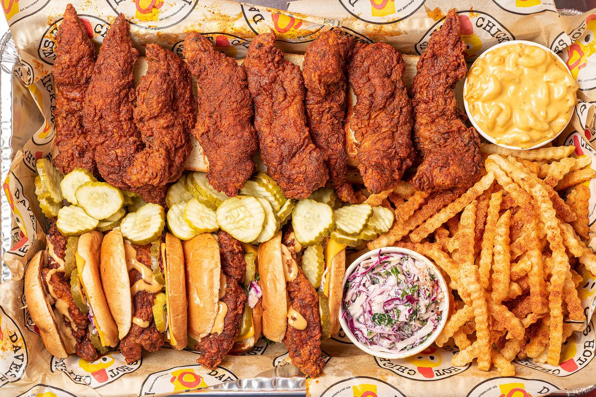 Hot chicken tenders on a tray divided by pickle chips with hot chicken sandwiches on the other side, french fries, cole slaw, and macaroni.