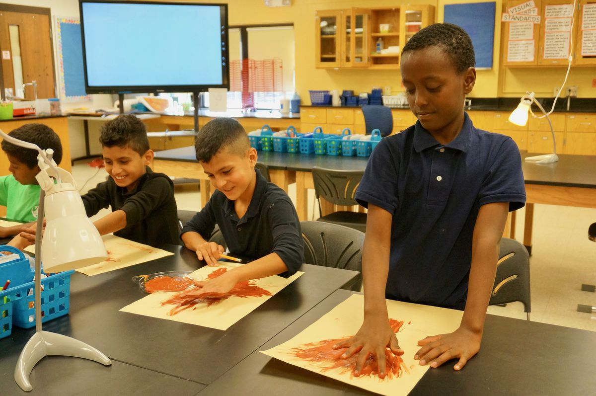 Students in the Indianapolis Public Schools newcomer program finger paint.