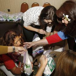 Deidre Henderson, a Utah Alternate Delegate (center in white top) and Janelle Yim, a delegate from Hawaii (far right) along with others box up humanitarian kits in Tampa, Florida.  The Republican National Convention was put on hold because of Hurricane Isaac but the Utah delegates used their extra time to put together humanitarian kits on Monday.  Delegates from Hawaii and Arizona helped out with the 1,000 hygiene kits and 100 back-to-school kits.  Monday, Aug. 27, 2012