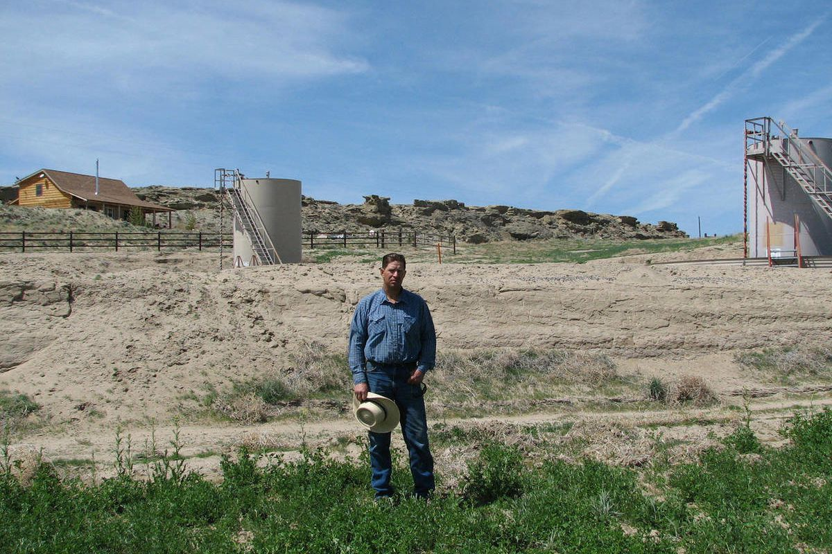 """In this May 22, 2009 photo shows John Fenton, a farmer who lives near the rural community of Pavillion in central Wyoming, outside his log home near a tank used in natural gas extraction. Fenton and some of his neighbors blame hydraulic fracturing, or """"fr"""
