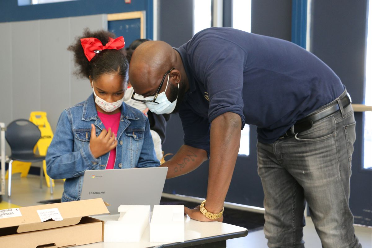 A male teacher helps a young student wearing a red bow in her hair on a laptop in their classroom.