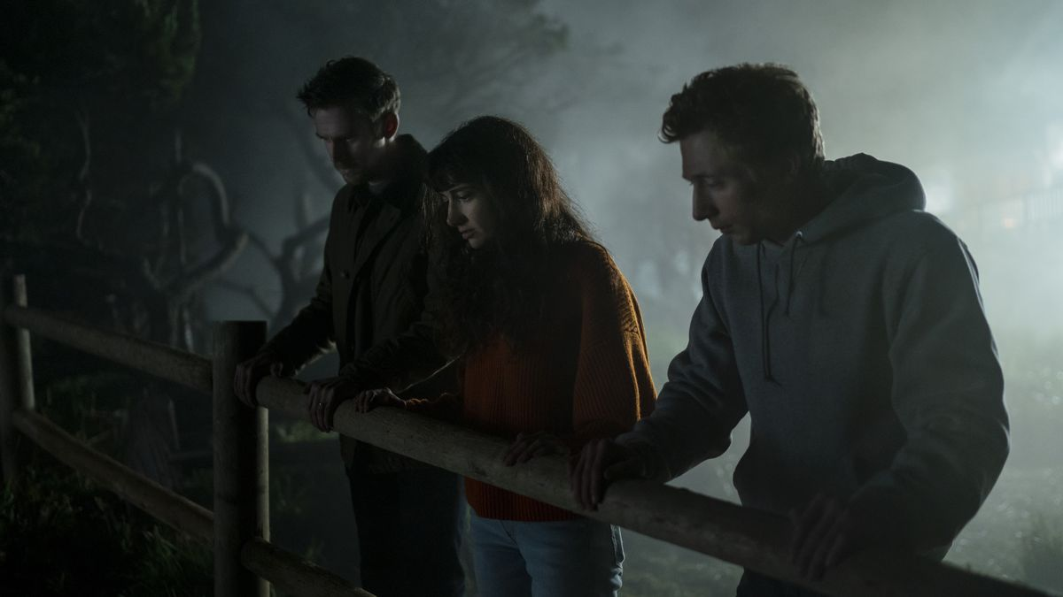 Two men in dark hoodies and a woman in a red sweater, standing in misty darkness, stand at a split-rail fence, looking down at something below.