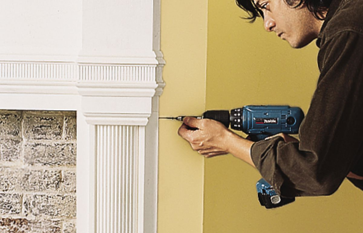Man Secures Mantel With Phillips Screwdriver And Screws
